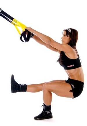 Image of a female trainee using a suspension trainer for suspension fitness workouts.