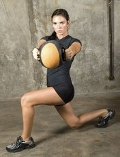 Image of a female client training gym-free with a medicine ball.
