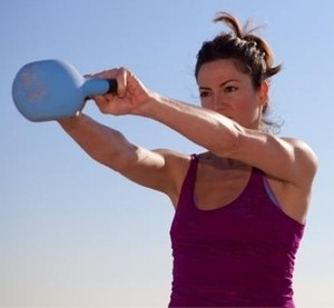 A female client training with a kettlebell outdoors.
