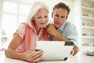 Image of a middle-aged couple looking at their online personal training programs.