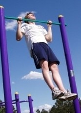 Image of a male fitness client doing a gym-free routine with pull-ups.