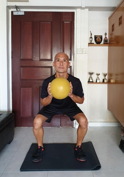 Image of a mid-life adult performing a functional squat.