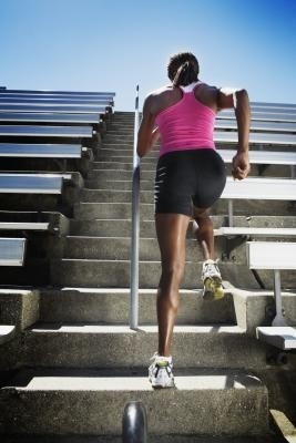 Image of a lady exercising on stadium stairs.