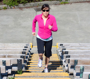 Image of a female fitness client performing stair-based exercises outdoors.