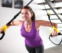 Image of woman exercising with a suspension trainer.